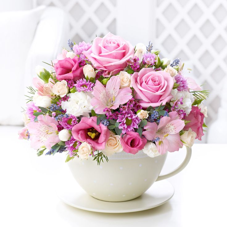 Pretty pastel coloured teacup table decoration.