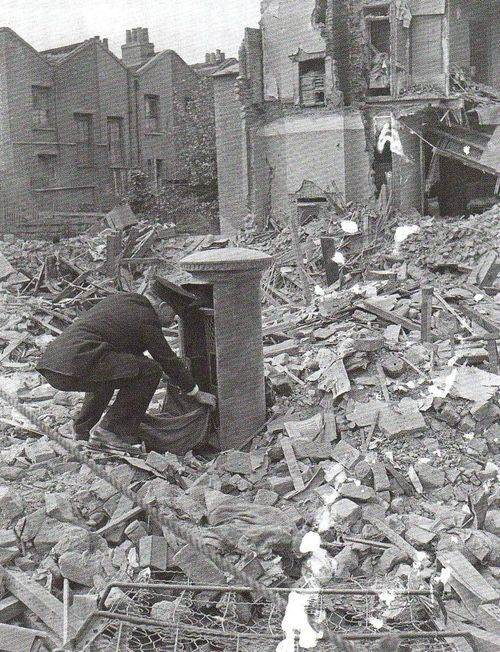 Postman collecting letters from a postbox in the middle of a bombed out street.