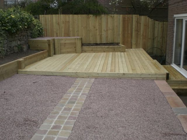 Decking raised sleeper planters fencing and indian stone for Garden decking