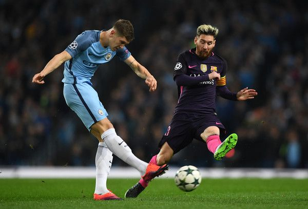 John Stones of Manchester City (L) shoots while Lionel Messi of Barcelona (R) attempts to block during the UEFA Champions League Group C match between Manchester City FC and FC Barcelona at Etihad Stadium on November 1, 2016 in Manchester, England.