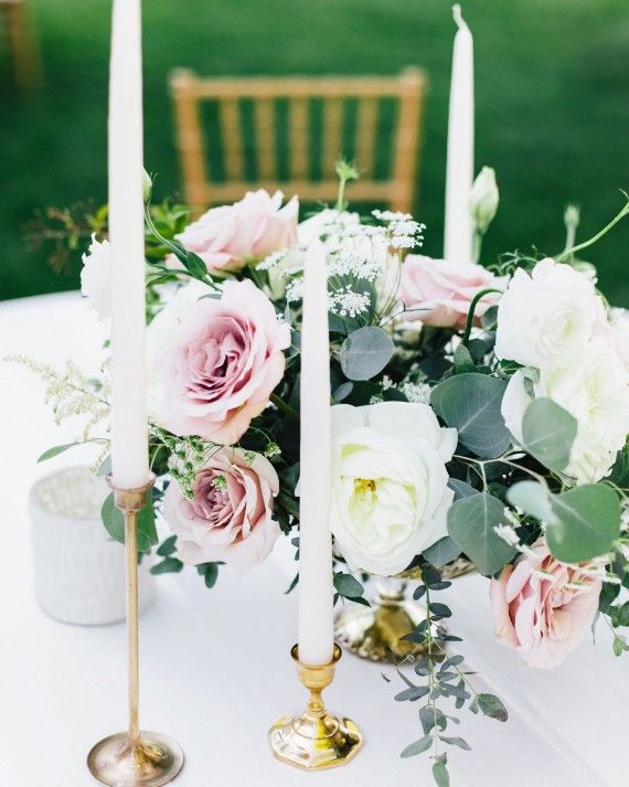 arrangements of soft pink and white roses in bud vases decorated the round tables along