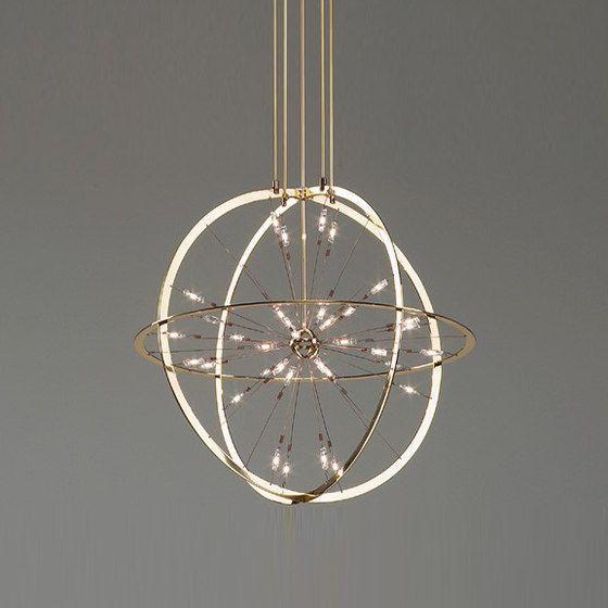 Naam: ARMILLA chandelier | Designer: Erik Lassen | Merk: Okholm Lighting | Land: Denemarken | Materiaal: Gepolijst en gelakt messing, chroom en spiegel | Kleur: goudkleur | Afmetingen: h240 x ø100cm | Mijn mening: Bij deze kroonluchter moest ik sterk denken aan een klok. Het lijkt alsof je wijzers ziet in een cirkel. Het is een mooi ruimtelijk product en door zijn asymmetrie krijg je een speels effect tussen de ringen. De gouden kleur straalt chiqueheid uit.