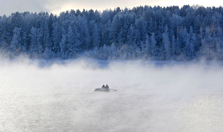Two men row a boat through a frosty fog along the Yenisei River at air temperature some minus 20 degrees Celsius outside the Siberian city of Krasnoyarsk, Russia.