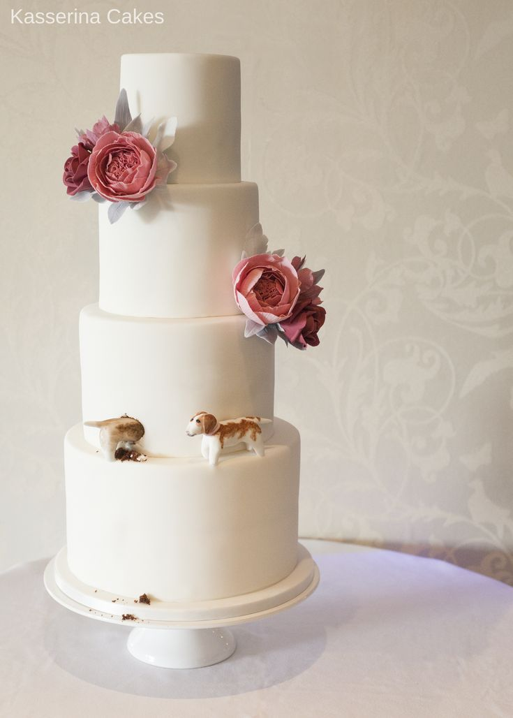 4 tier tall stacked wedding cake with dusky pink and grey sugar flower sprays and naughty dogs digging into cake by Sussex based, Kasserina Cakes.