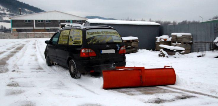 Snow plow towed behind a car