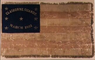 Flag: 2nd Alabama Infantry (Co. C, Claiborne Guards) Catalogue No. 86.3933.1  Provenance Reconstruction:  The flag of the Claiborne Guards was presented to the company on Saturday, March 23, 1861, at the Masonic Hall in Claiborne, Monroe County, Alabama, by seven young ladies, each of whom had been chosen to represent one of the seceded states. From them, Miss Henrietta Porcher Gaillard was selected to deliver the flag. Lt. E. A. Scott, professor at Columbus College in South Carolina and…