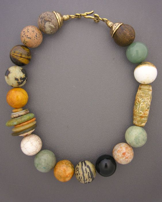 Necklace |  Anne Holland ~ Dorje Designs.    Stone beads made from agate, onyx, jasper, tigers eye,  and jade. A long carved serpentine bead. Discs made from jade, turquoise,  and other stones. And a fancy bronze hook and eye clasp.