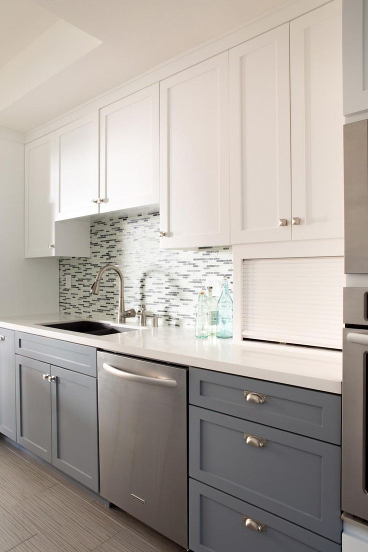 Light plays off the glass tile backsplash and stainless steel dishwasher and adds a sleek touch to this midcentury modern kitchen. White upper cabinets and gray lower ones bring additional visual interest to the space.