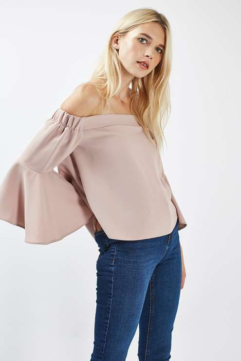 Off the shoulder is the trend to adopt today. This neutral putty bardot top is finished with an ultra-feminine flute sleeve that creates the perfect complement to a cigarette trouser.