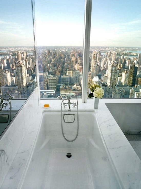 High-rise bathroom with amazing view. Bathroom features drop-in tub with marble surround and mirrored walls. Contemporary bathroom.