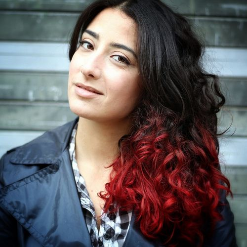 Long curly black hair with red dip dyed ends and a center part hairstyle