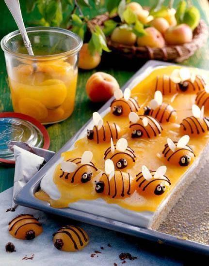 """Lite surr till kaffet blir det med den här söta kakan. En enklare variant är att grädda en sockerkaksmix. Täcka med färdig smörkräm som finns i välsorterade mataffärer, ofta på den amerikanska hyllan. Sedan bre på ett """"honungstäcke"""" av lemoncurd innan man placerar aprikoshalvorna med chokladlinjer och mandelvingar. Länk till receptet på tyska finns här."""
