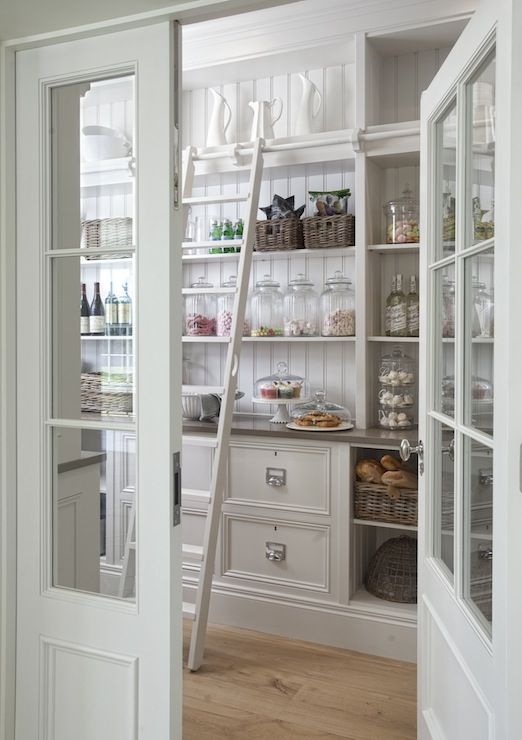 Fantastic pantry boasts white base cabinets flanked by open shelving filled with woven baskets topped with gray quartz countertops under built-in shelves lined with beadboard trim along with a ladder on rails