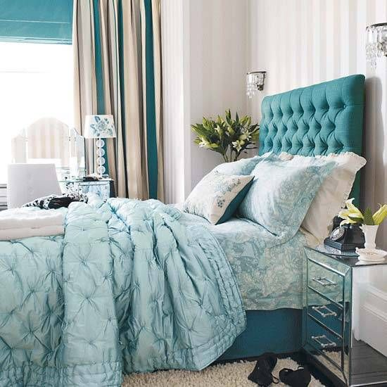 Upholstered bed headboard, bedding fabrics and window shades in turquoise blue color