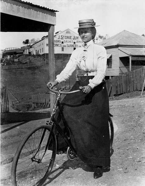 Woman cycling in Brisbane, 1890-1900  In the background are timber dwellings with a large shed belonging to J.Storie, who made window sashes, doors and mouldings.