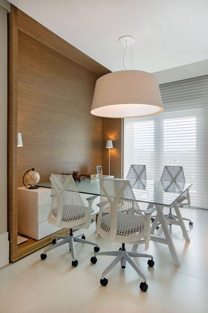 O office conta com uma mesa de reuniões feita com tampo de vidro apoiado no móvel planejado (Incomap Móveis) e em um cavalete todo revestido em couro pespontado (Le Cadeau Curtume Casa). Cadeiras Sayl, persianas Hunter Douglas Luxaflex (Délicatesse Tecidos) e pendente da Kelvin LD