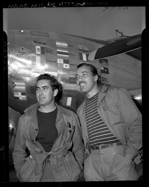 Actors Tyrone Power and Cesar Romero beside Power's plane on return from Latin-American good-will tour, 1946