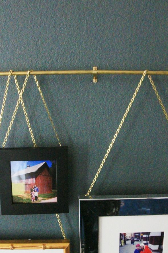 Affordable Framing and Easy DIY Picture Rail using brass rod, cafe curtain brackets, and plumbers chain.