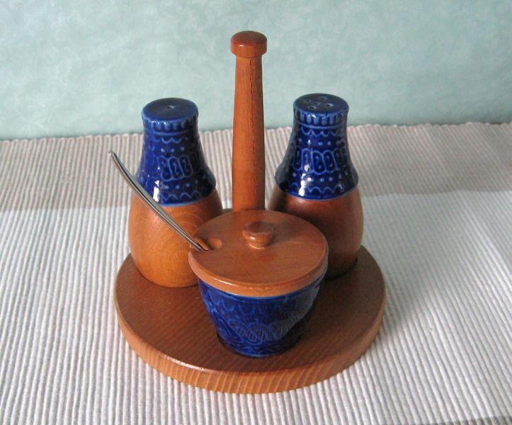 Menage Pfeffer Salz Senf Retro Danish Design. Tolle Menage bestehend aus Salzstreuer, Pfefferstreuer, Senftöpfchen mit Teakholz-Deckel und einem Serviertablett mit Holzgriff, ebenfalls aus Teak.  Die Menagerie im für die 60-er Jahre typischen skandinavischen Retro-Stil ist sehr gut erhalten, nur das Senftöpfchen hat innen einen Glasurriss, der die Funktionalität nicht beeinträchtigt. Sowohl Salz- als auch Pfefferstreuer können von unten befüllt werden. Größe gesamt: 12 x 13 cm