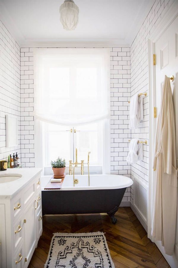 freestanding black tub with white subway tile and cabinets with gold fixtures