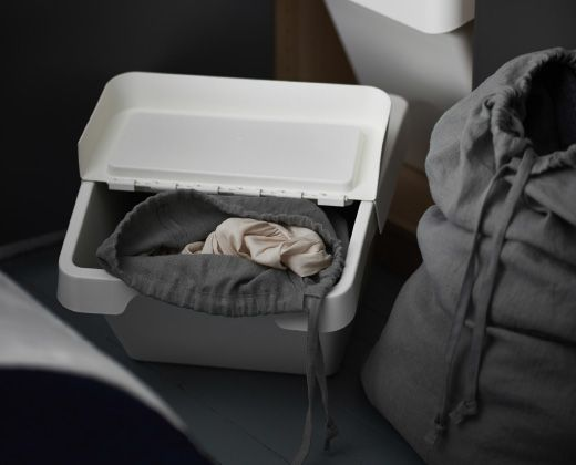 A close-up image of an IKEA SORTERA box with a fabric bag inside, used to store laundry.