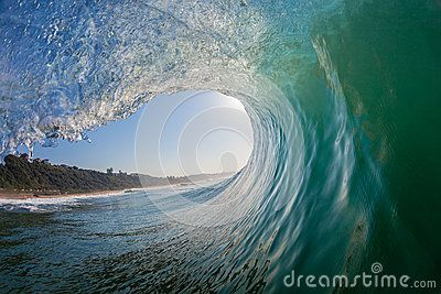Perfect moment from inside a hollow smooth glass wave wall of sea water curling surging over onto the shallow reef looking out towards the blue exit and  landscape. Water photography with wide angle lens in water-housing.
