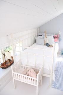 Valkoinen rautasänky/sohva, tyynyt, pupu ja merirosvolaiva pikkuikkunalla