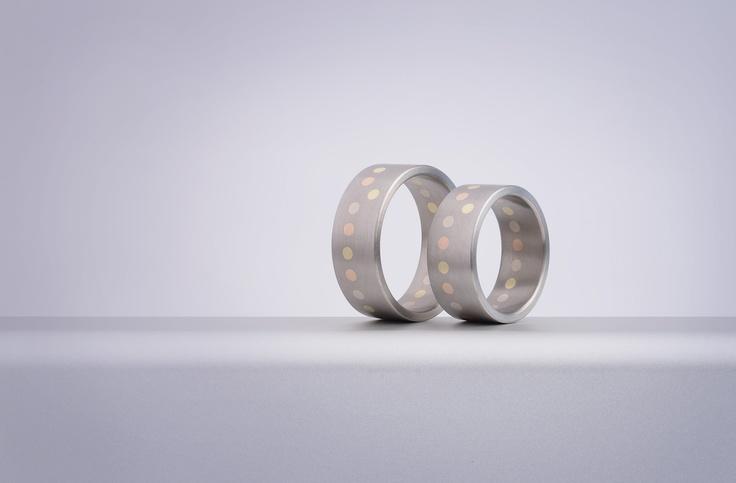 Snubní prsteny umí vyprávět příběh... Oba milují procházky svěží a sychravou podzimní přírodou, které jim vždy jejich prsteny připomenou. Tečky z barevného zlata evokují popadané vybarvené listí | Point kolekce Daloo