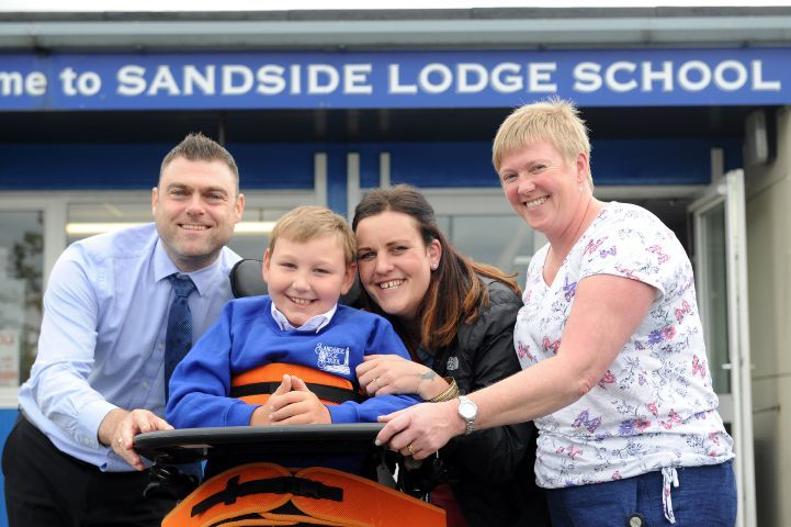 Mission: From left, CN group editor James Higgins presents Joe Morgan with a cheque for £1,000 from the Lake District Farmers Armstrong Family Charitable Trust, with Jo's mum Lianne Morgan and Janine Gray, senior teaching assistant at Sandside SchoolLEANNE BOLGER