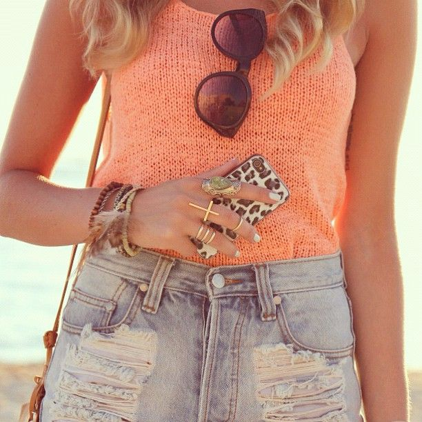 Coral knit top tucked into high-waisted jean shorts