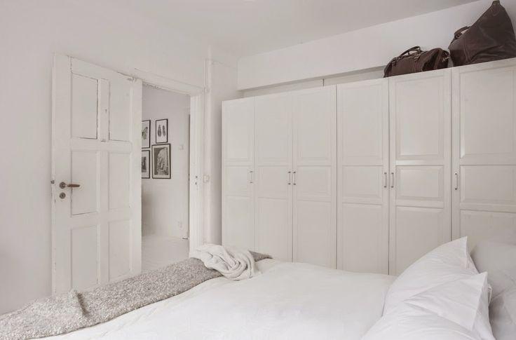 Białe szafy w aranżacji skandynawskiej sypialni