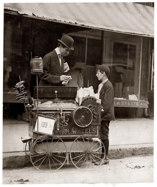 "Lewis Hine : ""Joseph Severio, peanut vendor, age 11 [seen with photographer Hine]. Been pushing a cart 2 years. Out after midnight on May 21, 1910. All earnings go to his father. Wilmington, Delaware."""