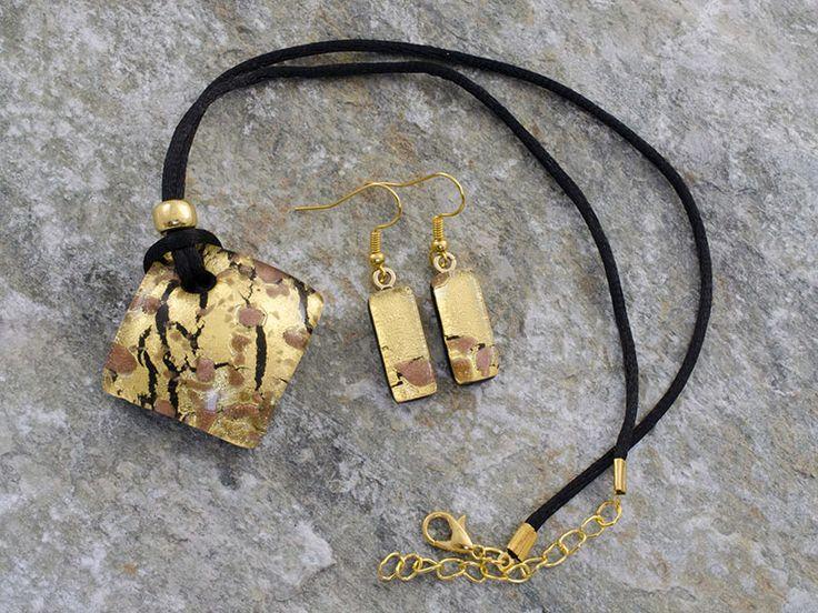 Parure in vetro di Murano con pendente rombo bombato ed orecchini rettangolari, laccio in cotone nero.   Di notevole eleganza, finezza e di gran pregio. Lo sfondo è composto da una foglia d'oro. In rilievo, striature nere e macchie color rame.