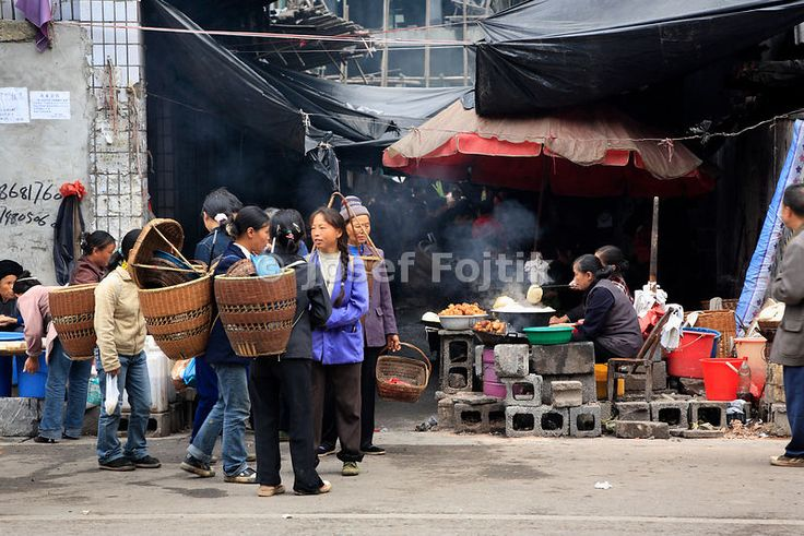 Women with back baskets on the street, Fenghuang town, Hunan, China