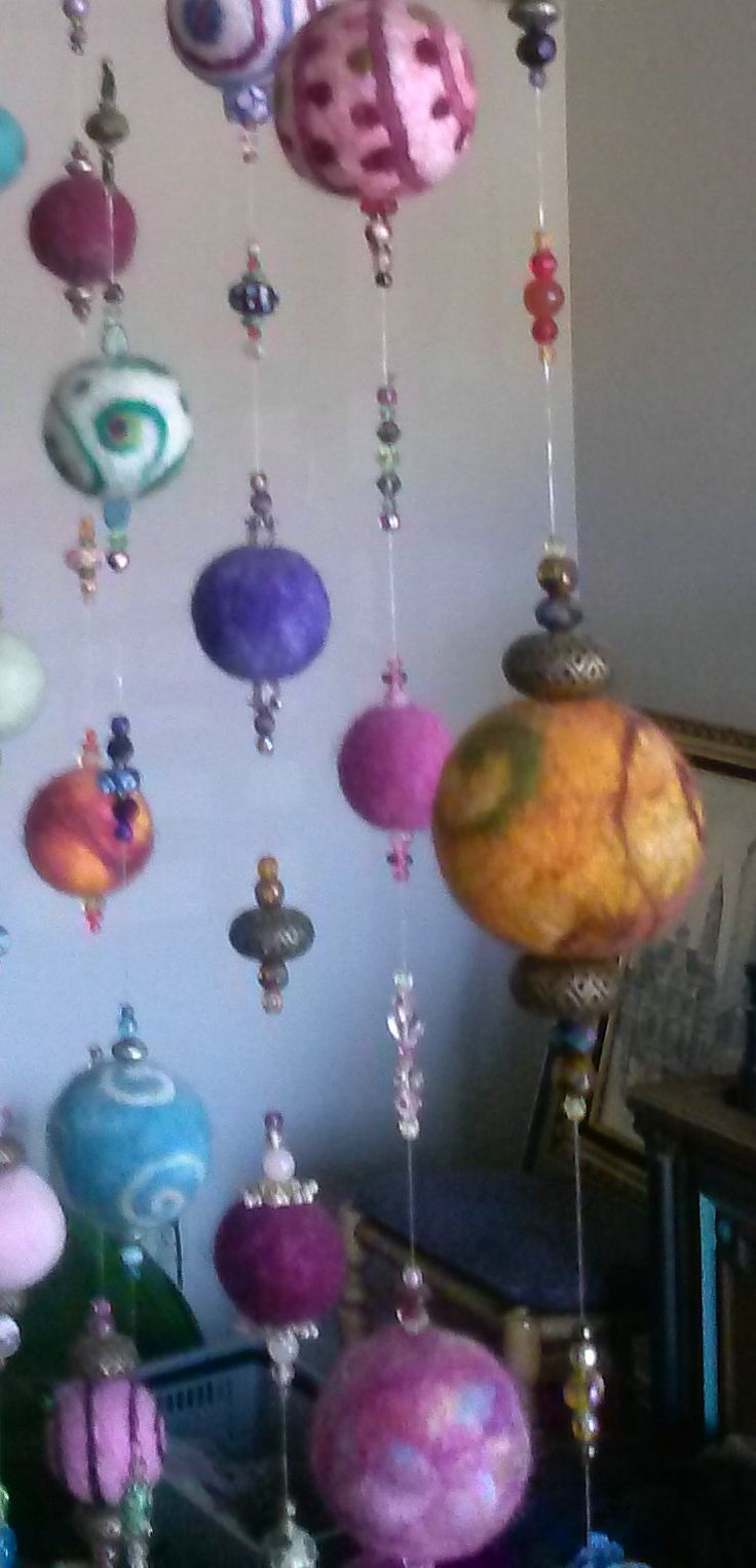 "I made 130 wool and silk & wool felted balls and strung them on fishing line with crystals & beads from my stash to make a ""curtain."" After lots of frustration, I found the perfect needle: the thinest tatting needle you can find. Long enough to go through the felt and fine enough to pass through a 4mm crystal twice."