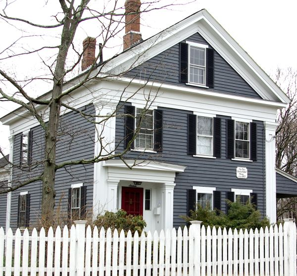 Adorable house with gray/blue siding, white trim, red door, and a picket fence.
