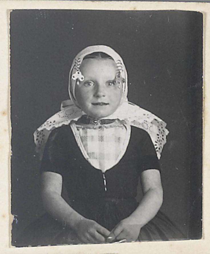 Meisje in Walcherse streekdracht. Onder de muts van broderie draagt ze een ondermuts met een oorijzer. Aan de 'krullen' (oorijzeruiteinden) hangen klaverbladvormige oorijzerhangers met een parel, de 'strikken'. In de uitsnijding van het jak zijn 'beuk' (kroplap) en schouderdoek te zien. Het meisje draagt om haar hals een halssnoer met vier strengen kralen aan een ronde sluiting. #Zeeland #Walcheren