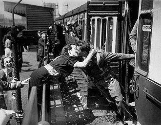 Una mujer se inclina sobre los rieles de un tren para besar a un soldado británico que regresa de la Segunda Guerra Mundial, Londres 1940.