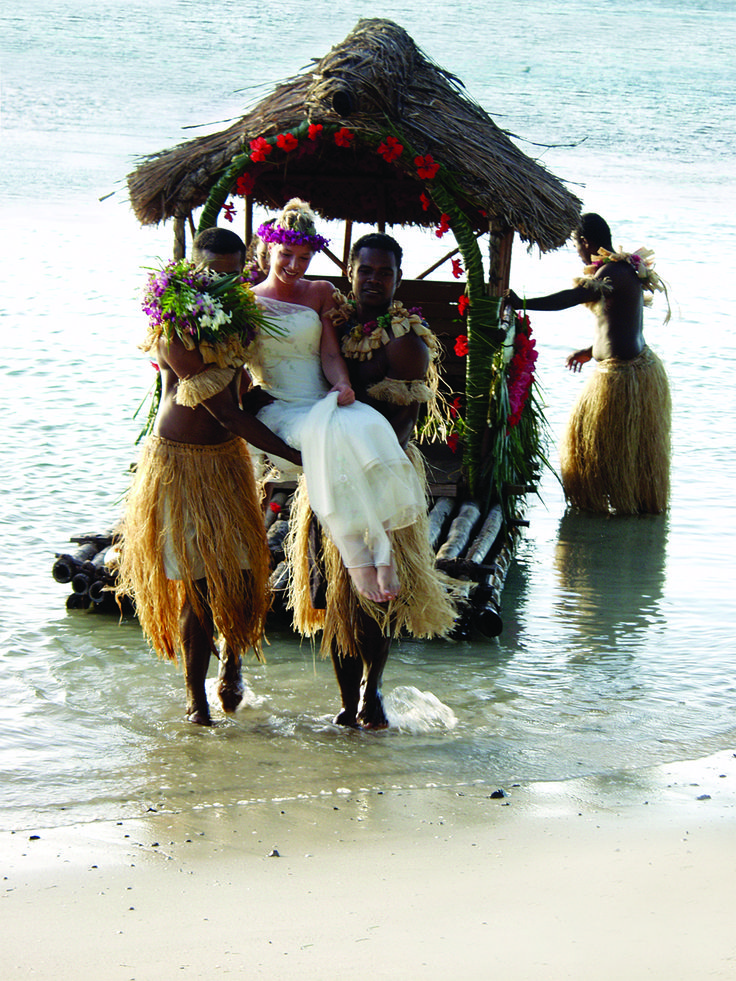 The bride alights from the billi billi for her wedding at Turtle Island Resort