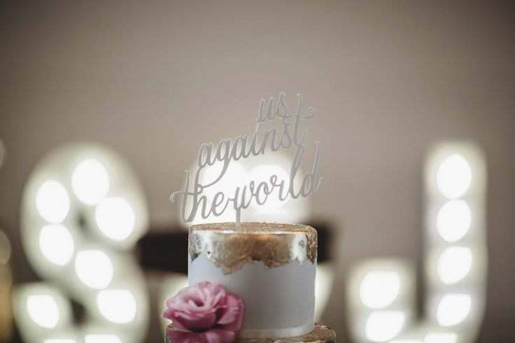 """White minimalist wedding cake with gold leaf and pink florals.  Cake topper """"Us against the world"""" by Communicake It. Shane and Jess's Melbourne town hall & Abbotsford convent wedding"""
