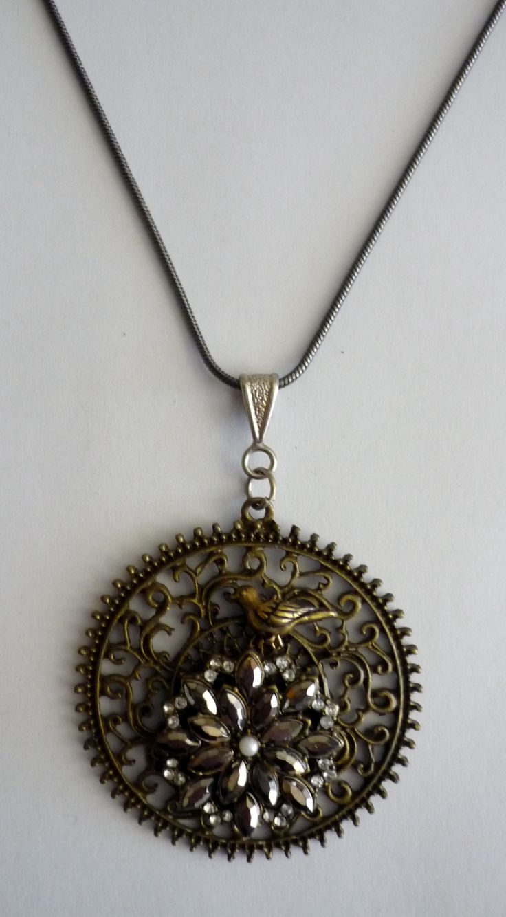Amanda Harris Large bronze filagree disk with silver diamonti in centre with gold dove on fine snake chain.