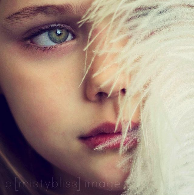 This girl totally looks like a child model with those eyes and feathers.