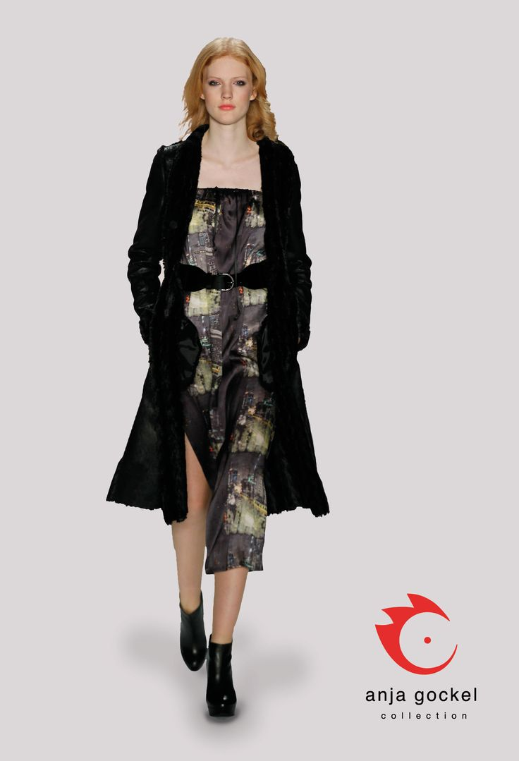 A splendid outfit consistent of a silken slited and sleeveless dress in a fascinating city print accentuated by a wide belt and a gorgeous fun fur top coat.