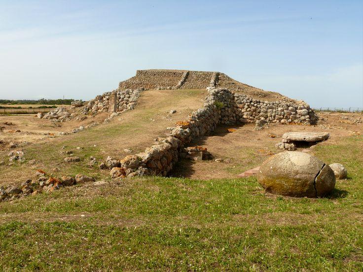 """Altare di Monte d'Accoddi. Si tratta di un santuario situato nel comune di Sassari e risalente al Neolitico medio (5.800-5.300 a.C.). Il nome """"akkoddi"""" si pensa derivi dal sardo arcaico """"Kodi"""", che significava """"monte"""". La struttura riportata in fotografia assume le caratteristiche dello ziqqurath mesopotamico e le pietre circolari presenti nel sito, di cui una si trova a destra dell'altare, si ipotizza simboleggiassero il Sole o la Luna."""
