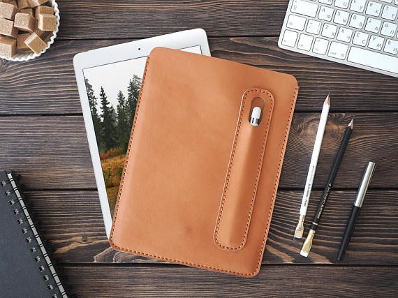 iPad Pro and Apple Pen holder. iPad leather case. iPad Pro 9.7 inch leather cover. Light brown color.  Cut, pierced and sewn by hand.  Your initials or other information can be added with stamping method.  SIZES: W*H 190*255 mm, (7.4*10 in)  Genuine leather, 2 mm, waxed thread.  What makes this case so great? – protection of your iPad from scrtatches, – minimalistic design, – neat handwork, – lasting and smooth to touch leather.  TREATMENT: with colourless leather cream or colourless spray…