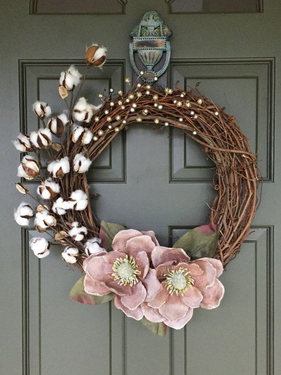 A simple yet so elegant pink magnolia flower wreath with a sprig of cotton (Southern Charm?) finished with a sparkly gold and champagne pink berry