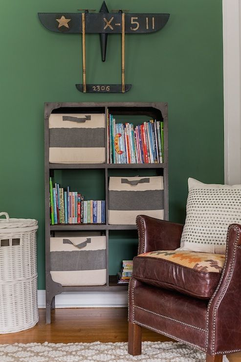 Lovely boy's room features hunter green paint on walls framing vintage airplane over industrial bookcase filled with ivory and grays rugby striped bins and books next to white wicker hamper and brown leather chair with nailhead trim atop white and beige trellis rug.