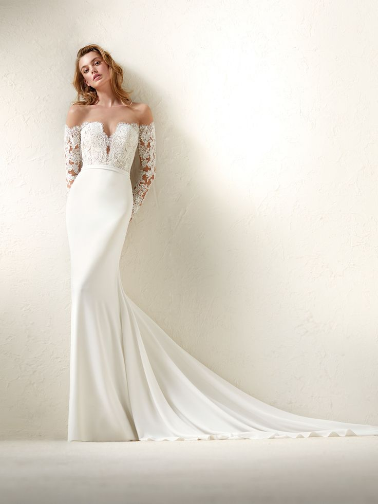 Beautiful off the shoulder lace Pronovias fit and flare gown. To schedule an appointment with us call 515-244-2266