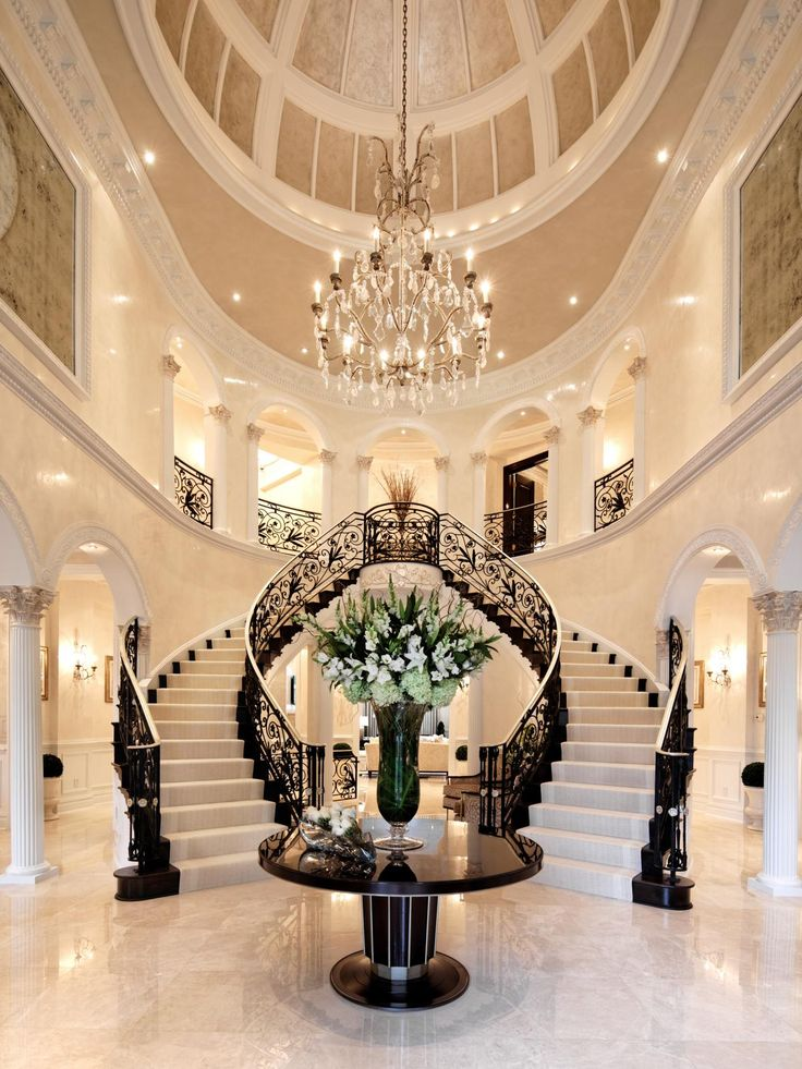 A spacious foyer with a domed ceiling and double staircase makes a grand entrance to this home. An elegant chandelier and black and white staircase complete the classic look.
