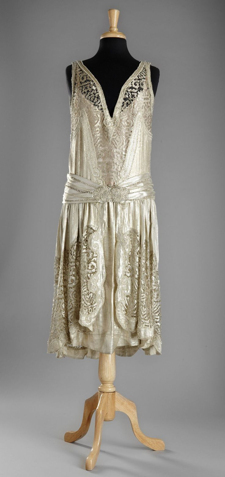 CHARLESTON DRESS, ca. 1924 of gold lamé an metallic lace embroidered with crystals and pearls.
